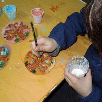 Bambini al lavoro per realizzare la bomboniera d'artista per la prima comunione presso il Laboratorio ArtiBus di Vasto